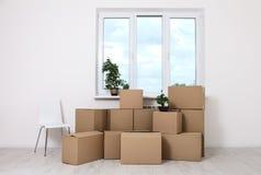 Flytta sig in i en ny lägenhet Flytta massor av kartonger i en tom ny lägenhet Arkivfoton