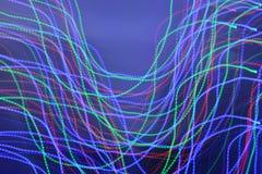 Flyttande ljus mot blå bakgrund - olika färger arkivbilder