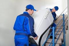 Flyttkarlar som bär kylskåpet på moment royaltyfri bild