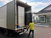 Flyttkarlar som lastar av en rörande skåpbil Arkivbilder