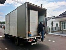 Flyttkarlar som lastar av en rörande skåpbil Arkivfoto