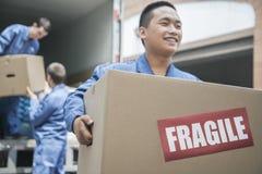 Flyttkarlar som lastar av en rörande skåpbil och bär en bräcklig ask Arkivfoton