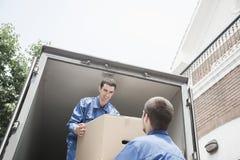 Flyttkarlar som lastar av en rörande skåpbil som passerar en kartong Arkivbilder