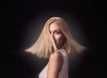 Flyttning för blont hår för huvud för framsida för ung flickamodemodell Arkivfoto