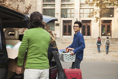 Flyttning för ung man in i sovsal på högskolauniversitetsområde royaltyfria bilder
