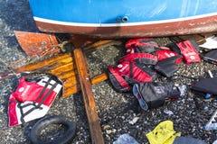 Flytvästar kasserade på en strand Flyktingar kommer från Turkiet i ett uppblåsbart fartyg Arkivfoton
