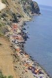 Flytvästar och fartyg som lämnas på den grekiska stranden av flyktingar Arkivfoto