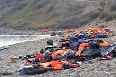 Flytvästar och fartyg som lämnas på den grekiska stranden av flyktingar Royaltyfri Fotografi