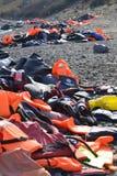 Flytvästar och fartyg som lämnas på den grekiska stranden av flyktingar Royaltyfria Foton