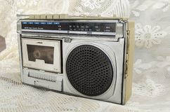 AM FM Radio Cassette Recorder. Old silver and black AM FM radio and cassette recorder with analog tuning wheel on ivory color floral laced fabric stock photography