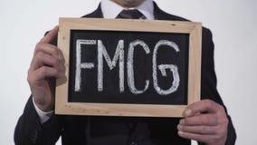 FMCG written on blackboard in businessman hands, consumer goods, retail trade. Stock footage stock video