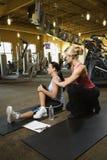 Fêmea adulta com instrutor pessoal. Fotografia de Stock