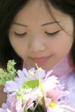 Fêmea asiática bonita com flores Fotografia de Stock Royalty Free