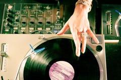 Fêmea DJ na plataforma giratória no clube Imagens de Stock