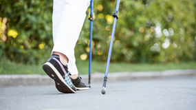 A fêmea em sapatas pretas que anda com seguimento cola Fotografia de Stock Royalty Free