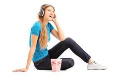 Fêmea loura que escuta uma música e que come a pipoca Foto de Stock