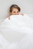 Fêmea na cama que esconde atrás do cobertor Foto de Stock