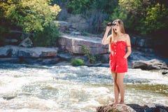 Fêmea surpreendida jovens que usa binóculos no Fotos de Stock