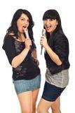 Fêmeas modernas que cantam nos microfones Imagens de Stock