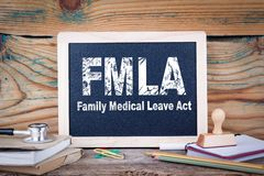 Fmla, family medical leave act. Chalkboard on a wooden background