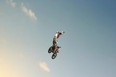 FMX-Radfahrer, der auf einen Hintergrund des Himmels springt Lizenzfreies Stockbild