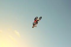 FMX-Radfahrer, der einen hinteren leichten Schlag auf einem Hintergrund des blauen Himmels tut Stockfotos