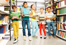 Fünf Freunde mit Stapel von Büchern in der Bibliothek Stockfotos