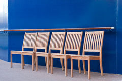 Fünf hölzerne Stühle durch blaue Schottwand Stockbilder