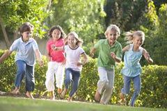 Fünf junge Freunde, die draußen lächeln laufen lassen Lizenzfreies Stockfoto