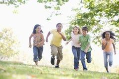 Fünf junge Freunde, die draußen lächeln laufen lassen Lizenzfreie Stockbilder