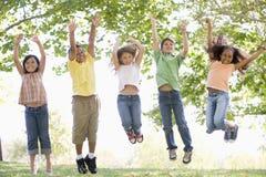 Fünf junge Freunde, die draußen lächeln springen Lizenzfreie Stockfotografie