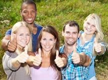 Fünf junge Leute, die sich Daumen zeigen Lizenzfreie Stockbilder