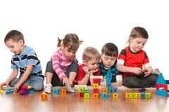 Fünf Kinder, die auf dem Boden spielen Stockbild
