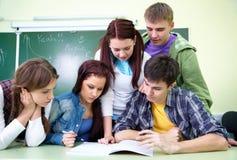 Fünf Kursteilnehmer im Klassenzimmer Stockbilder