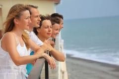 Fünf lächelnde Freunde auf Balkon Lizenzfreies Stockfoto
