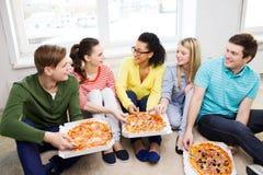 Fünf lächelnde Jugendliche, die zu Hause Pizza essen Stockfoto