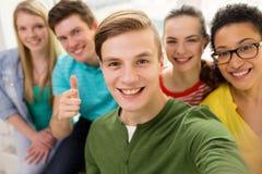 Fünf lächelnde Studenten, die in der Schule selfie nehmen Lizenzfreie Stockfotos