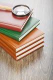 Fünf Notizbücher und Vergrößerungsglas Stockfoto