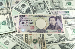 Fünf tausend Anmerkungen der japanischen Yen über Hintergrund vieler Dollar Stockfotos