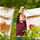 Fünfjahresmädchen mit Clothespin und der Wäscheleine Lizenzfreie Stockbilder