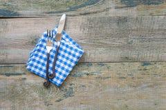 Fnife、叉子和餐巾在木背景 免版税库存图片