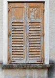 Fönster av gammal byggnad som täckas av trärullgardiner med skalningsmålarfärg Arkivfoton