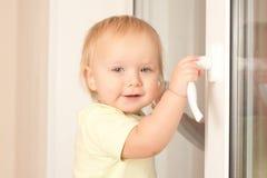 fönster för litet barn för flickaholdingknopp Fotografering för Bildbyråer