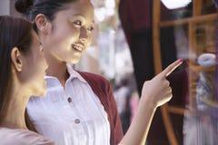Fönstershopping för två unga kvinnor Arkivbild
