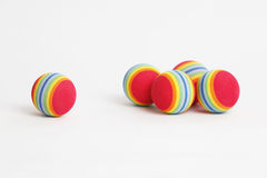Foam Balls. 5 colourful foam balls scattered on a white background. sharp focus on the lone ball. Image shot on 5D Mark II and L lens stock image