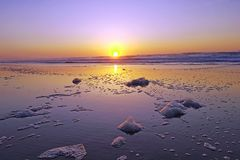 Foam on the beach at sunset Royalty Free Stock Image