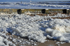 Foam on beach from waves. A mass of sea water whipped up into foam blowing up against sea defences Stock Photography