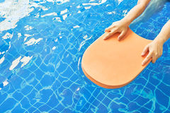 Foam board and hands in the middle of the pool, which is a niche for swimming practice Stock Photo