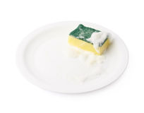Foam covered sponge over ceramic plate. Foam covered dish washing kitchen sponge over the surface of the white ceramic plate, composition isolated over the white royalty free stock photography
