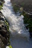 Foam crash. Waves and sea foam crashing though granite slot and foam covered shore Royalty Free Stock Photo